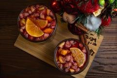 Wohlriechendes würziges traditionelles Getränk in einem Glasbecher, Glühwein, mit einem Weihnachtsbaum, Gewürzen und frischen Frü stockfoto