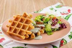 Wohlschmeckende belgische Waffeln mit Käsesoße und -salat Stockbilder