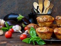 Wohlschmeckende Muffins des Snacks backt mit Aubergine, Tomaten, Basilikum und Käse auf hölzernem Hintergrund zusammen Lizenzfreie Stockfotografie