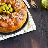 Wohlschmeckende Torte, rundes Affebrot mit angefüllten Brötchen oives und der Käse, überstiegen mit geriebenem Käse und schwarzer lizenzfreies stockfoto