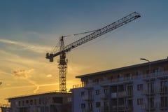 Wohnblock im Bau mit Kran am Sonnenunterganghimmel, Fristenkonzept treffend Stockfotografie