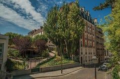 Wohngebäude und bewaldete Gärten unter sonnigem blauem Himmel in einer Straße von Montmartre in Paris stockbild