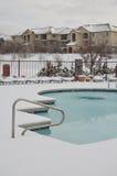 Wohnungen und Swimmingpool im Schnee stockbilder