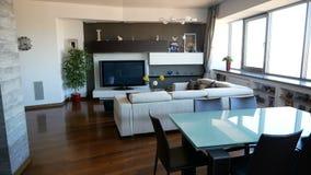 Wohnungsinnenraum mit Sofa, moderner Tabelle mit Stühlen und Fernsehen stock video footage