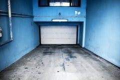 Wohnuntertagegarage mit weißer Tür und blauen Wänden Parken unter dem Wohngebäude lizenzfreie stockbilder