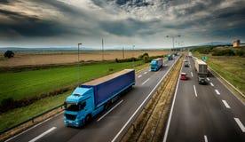 Wohnwagen oder Konvoi von blauen Lastwagen-LKWs auf Landstraße lizenzfreie stockbilder