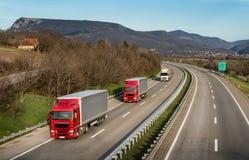 Wohnwagen oder Konvoi von LKWs auf Landstraße stockfotos