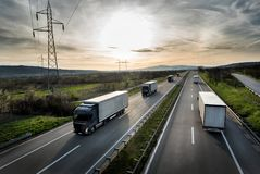 Wohnwagen oder Konvoi von LKWs auf Landstraße stockbilder