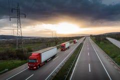 Wohnwagen oder Konvoi von roten LKWs auf Landstraße lizenzfreies stockfoto
