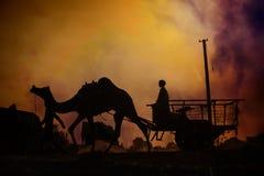 Wohnwagen von Kamelen bei Sonnenuntergang in der Sandwüste Stockbild