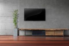 Wohnzimmer führte Fernsehen auf Betonmauer mit Holztisch Stockfotografie