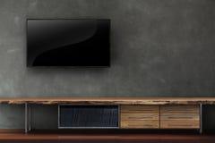 Wohnzimmer führte Fernsehen auf Betonmauer mit Holztischmedien furn Stockfoto