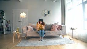 Wohnzimmer mit einer jungen Frau, die auf VR-Gläser sich setzt stock video footage