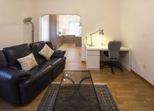Wohnzimmer mit schwarzem ledernem Sofa und Parkett lizenzfreie stockfotos