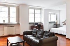 Wohnzimmer, schwarzes ledernes Sofa lizenzfreie stockbilder