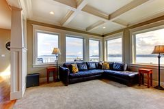 Wohnzimmer wih viele großen Fenster und blaues Sofa. Stockbild