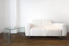 Wohnzimmerdetail mit einem Sofa des weißen Leders Stockfotografie