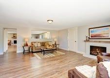Wohnzimmerinnenraum des offenen Grundrisses in den weißen Tönen mit Massivholzboden lizenzfreies stockbild