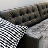 Wohnzimmerinnenraum, dunkles ledernes Sofa mit weichem Kissen stockfoto