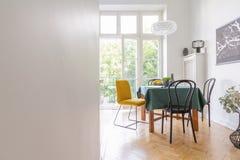 Wohnzimmerinnenraum mit Tischdecke und unterschiedliche Art von Stühlen, schwarze Karte auf der Wand, wirkliches Foto mit lizenzfreies stockbild