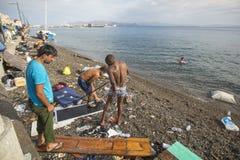 Wojenni uchodźcy myją up na plaży Wiele uchodźcy przychodzący od Turcja w nadmuchiwane łodzie Zdjęcie Stock