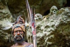 Wojownik Papuaski plemię Yafi w tradycyjnych ubraniach, ornamentach i kolorystyce, Czaszki tło Fotografia Royalty Free