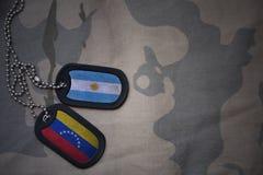 wojska puste miejsce, psia etykietka z flaga Argentina i Venezuela na khakim tekstury tle, Zdjęcie Royalty Free