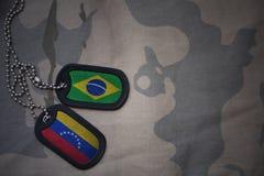 wojska puste miejsce, psia etykietka z flaga Brazil i Venezuela na khakim tekstury tle, Obrazy Stock