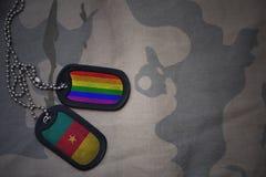 wojska puste miejsce, psia etykietka z flaga Cameroon i homoseksualna tęcza, zaznaczamy na khakim tekstury tle Zdjęcie Stock