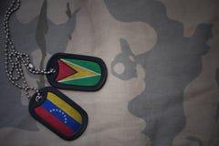 wojska puste miejsce, psia etykietka z flaga Guyana i Venezuela na khakim tekstury tle, Zdjęcia Royalty Free