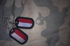 Wojska puste miejsce, psia etykietka z flaga Indonesia na khakim tekstury tle fotografia royalty free