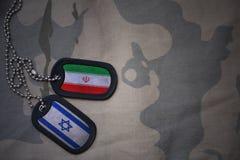 wojska puste miejsce, psia etykietka z flaga Iran i Israel na khakim tekstury tle, Zdjęcie Stock