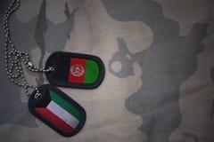 wojska puste miejsce, psia etykietka z flaga Kuwait i Afghanistan na khakim tekstury tle, Obrazy Royalty Free