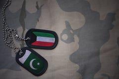 wojska puste miejsce, psia etykietka z flaga Kuwait i Pakistan na khakim tekstury tle, Obrazy Stock