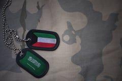 wojska puste miejsce, psia etykietka z flaga Kuwait i saudyjczyk Arabia na khakim tekstury tle, Zdjęcia Royalty Free