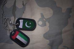 wojska puste miejsce, psia etykietka z flaga Pakistan i zlani arabscy emiraty na khakim tekstury tle, Obraz Royalty Free