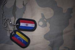 wojska puste miejsce, psia etykietka z flaga Paraguay i Venezuela na khakim tekstury tle, Fotografia Royalty Free