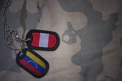 wojska puste miejsce, psia etykietka z flaga Peru i Venezuela na khakim tekstury tle, Zdjęcia Stock
