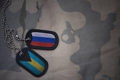 wojska puste miejsce, psia etykietka z flaga Russia i Bahamas na khakim tekstury tle, Fotografia Stock