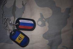 wojska puste miejsce, psia etykietka z flaga Russia i Barbados na khakim tekstury tle, Fotografia Royalty Free