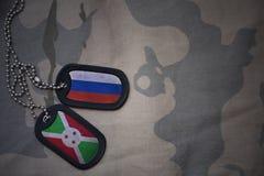 wojska puste miejsce, psia etykietka z flaga Russia i Burundi na khakim tekstury tle, Obrazy Royalty Free
