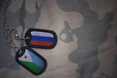 wojska puste miejsce, psia etykietka z flaga Russia i Djibouti na khakim tekstury tle, Zdjęcie Royalty Free