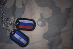 wojska puste miejsce, psia etykietka z flaga Russia i el Salvador na khakim tekstury tle, Zdjęcia Royalty Free