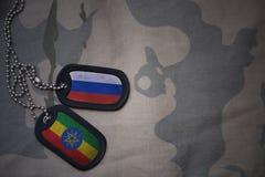 wojska puste miejsce, psia etykietka z flaga Russia i Ethiopia na khakim tekstury tle, Zdjęcia Royalty Free