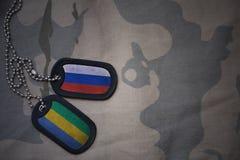 wojska puste miejsce, psia etykietka z flaga Russia i Gabon na khakim tekstury tle, Zdjęcie Royalty Free