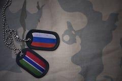 wojska puste miejsce, psia etykietka z flaga Russia i Gambia na khakim tekstury tle, Zdjęcia Royalty Free
