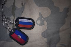 wojska puste miejsce, psia etykietka z flaga Russia i Haiti na khakim tekstury tle, Zdjęcia Stock
