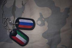 wojska puste miejsce, psia etykietka z flaga Russia i Kuwait na khakim tekstury tle, Obraz Stock