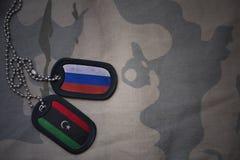 wojska puste miejsce, psia etykietka z flaga Russia i Libya na khakim tekstury tle, Obrazy Stock