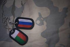 wojska puste miejsce, psia etykietka z flaga Russia i Madagascar na khakim tekstury tle, Obrazy Royalty Free